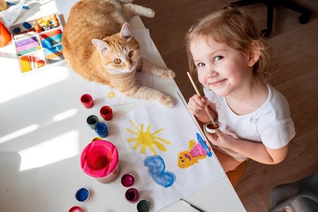 Uma menina pinta o sol e sua mãe com aquarelas um gato ruivo deita ao lado da mesa.