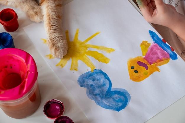 Uma menina pinta o sol e sua mãe com aquarelas
