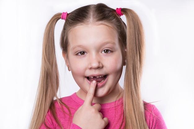 Uma menina pré-escolar com seus primeiros incisivos adultos