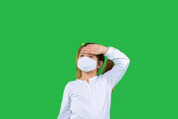 Uma menina pré-escolar com uma máscara protetora franzindo os olhos segura sua cabeça e olha para longe