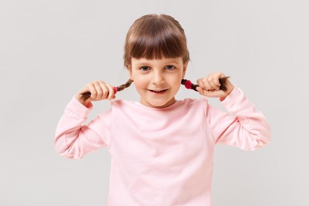 Uma menina pré-escolar fofa olha para a frente com um sorriso