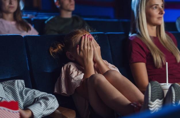 Uma menina preocupada com a mãe cobrindo os olhos no cinema enquanto assistia ao filme.