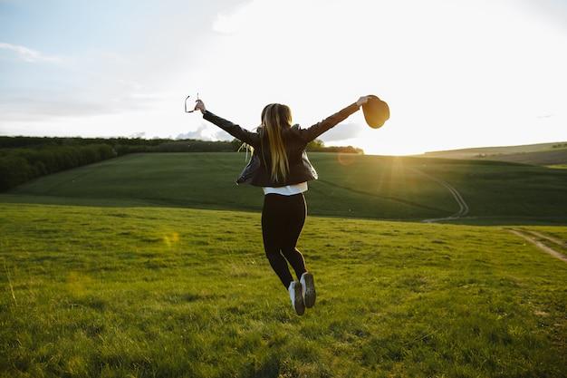 Uma menina pulando de alegria ao pôr do sol