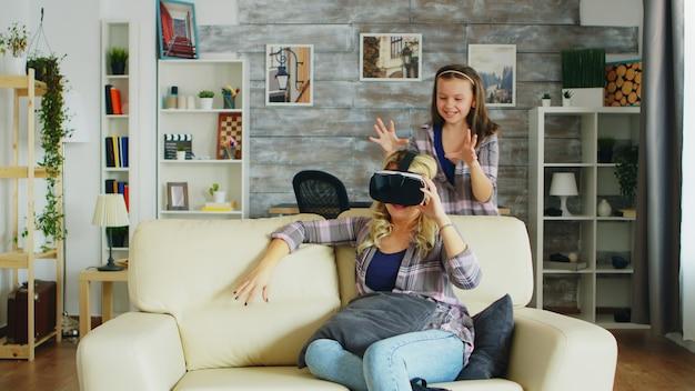 Uma menina pulando em volta de sua mãe enquanto ela está usando um fone de ouvido de realidade virtual, sentada no sofá.