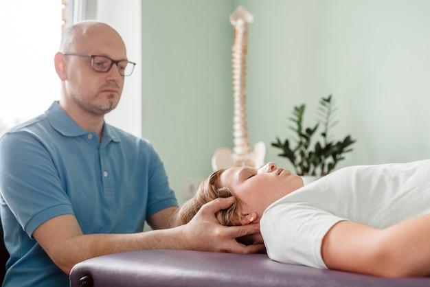 Uma menina recebendo tratamento cst por um osteopata usando uma técnica prática suave, alívio da tensão do sistema nervoso central