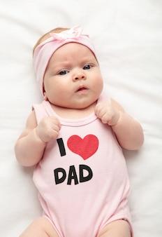 Uma menina recém-nascida com uma camiseta com a inscrição eu amo o pai olhando para a câmera