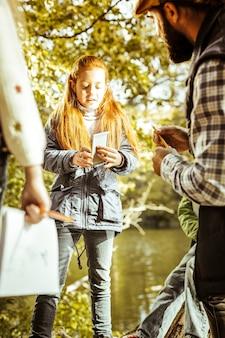 Uma menina ruiva pensativa durante uma aula de floresta em um dia bom