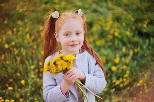 Uma menina ruivo bonito pequena no fundo de um campo dos dentes-de-leão e das hortaliças.