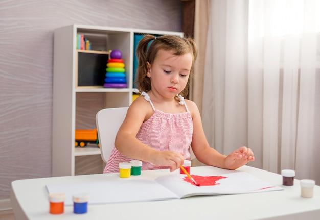 Uma menina se senta a uma mesa e desenha na mesa com um pincel e tintas
