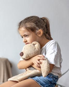 Uma menina se senta e segura um ursinho de pelúcia com força nas mãos.