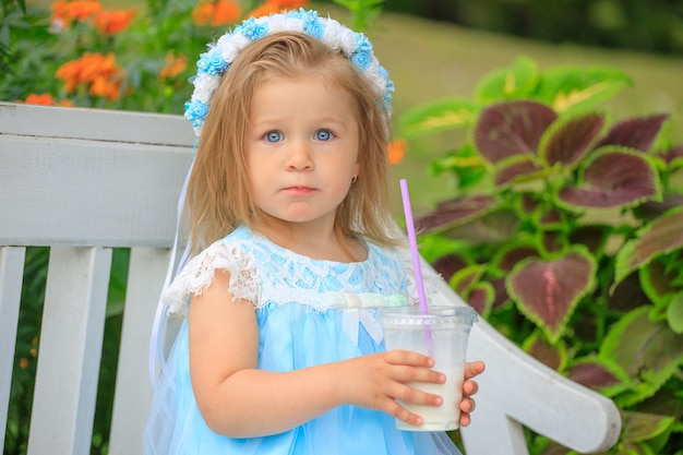 Uma menina se senta em um banco com um vestido azul e bebe um milkshake