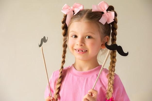 Uma menina segura máscaras de fantasias para o dia dos pais.