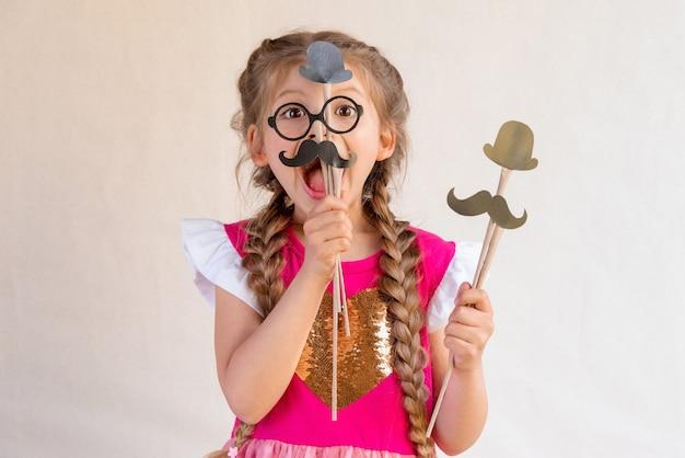 Uma menina segura máscaras de máscaras para o feriado do dia dos pais.