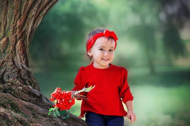 Uma menina segura um buquê de cinzas da montanha vermelha nas mãos.