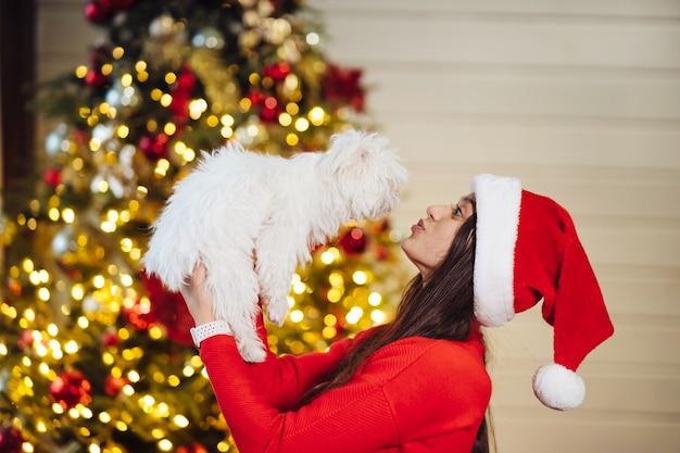 Uma menina segura um cachorrinho nas mãos na árvore de natal