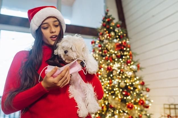 Uma menina segura um cachorrinho nas mãos na véspera de ano novo com um amigo