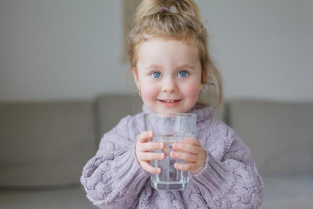 Uma menina segura um copo de água, bebidas. aconchegante.