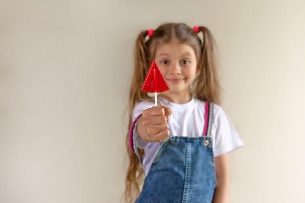 Uma menina segura um pirulito vermelho na mão.