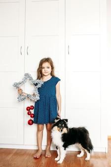 Uma menina segura uma estrela nas mãos para decorar a casa para o ano novo e o natal, um cachorrinho cachorrinho criança shelty se preparando para o feriado, ajudando os pais, esperando por presentes
