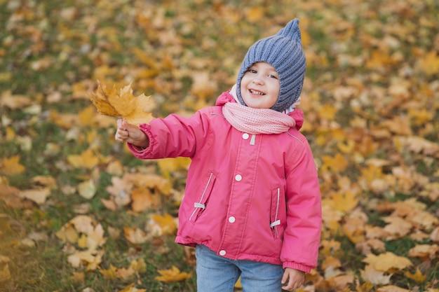 Uma menina segura uma folha de bordo de outono em suas mãos foto brilhante de outono no parque com folhas de ...