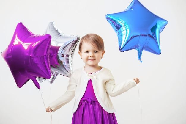 Uma menina segurando balões em forma de estrelas