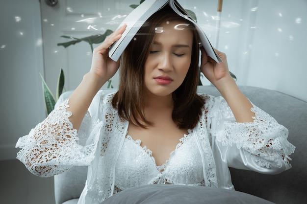 Uma menina segurando seu livro sobre a cabeça, cansada de ler e com sono