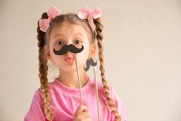 Uma menina segurando um bigode artificial. e faz uma careta.