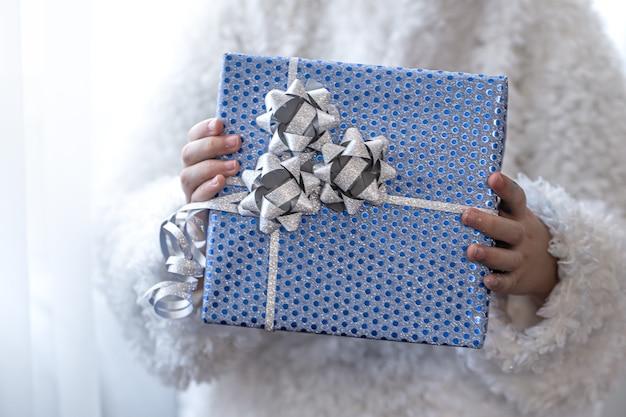 Uma menina segurando um presente de feriado azul.