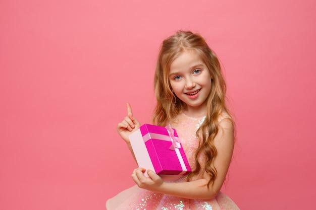 Uma menina segurando um presente nas mãos sorri em um espaço rosa.
