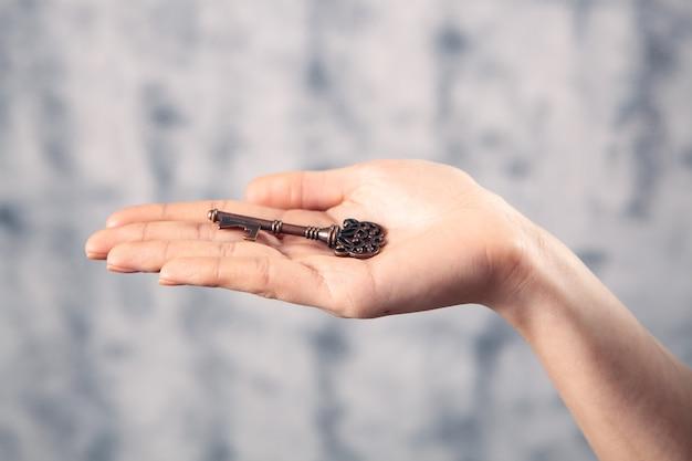 Uma menina segurando uma chave velha na mão