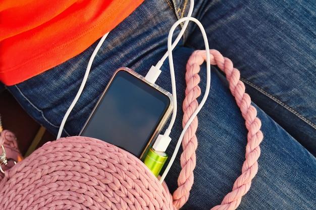 Uma menina senta-se em um banco no parque enquanto carrega um smartphone de um banco de energia externo