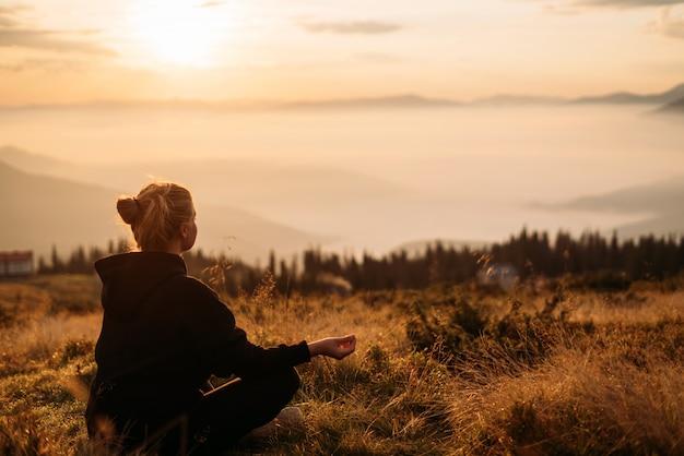 Uma menina senta-se na grama em uma pose de meditação, aguardando o amanhecer