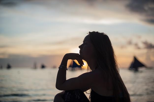 Uma menina senta-se na praia na ilha de boracay