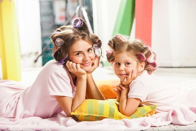 Uma menina sentada com a mãe dela e jogando