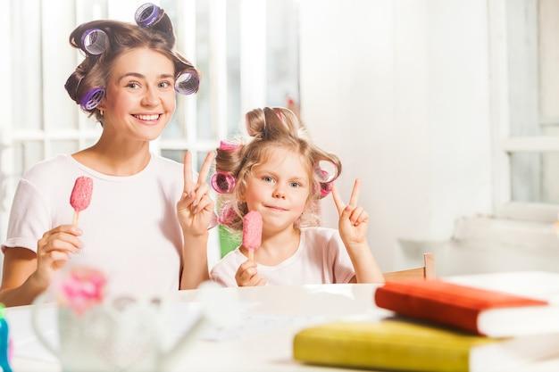 Uma menina sentada com a mãe tomando sorvete