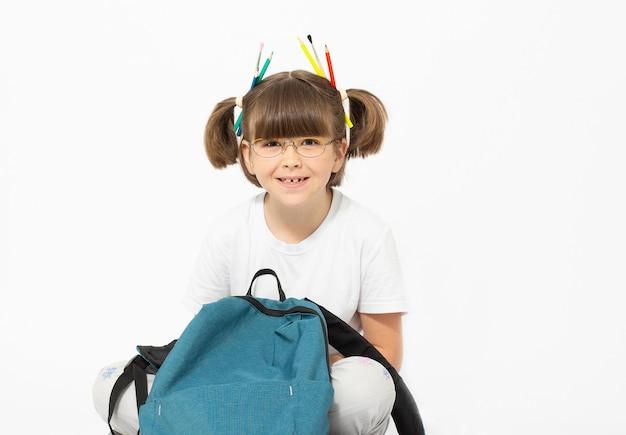 Uma menina sentada com sua mochila escolar e lápis de superfície branca