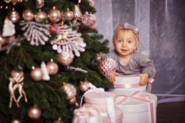 Uma menina sentada debaixo da árvore de natal. ela abraça as mãos caixas de presente de natal