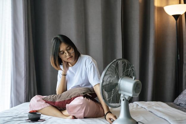 Uma menina sentada e tomando café no quarto.