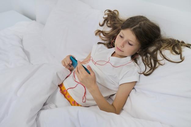 Uma menina sentada em casa na cama, com smartphone e fones de ouvido