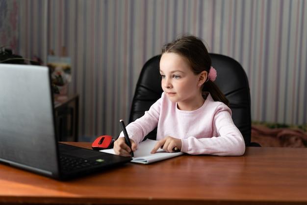 Uma menina sentada em casa segurando uma caneta nas mãos.