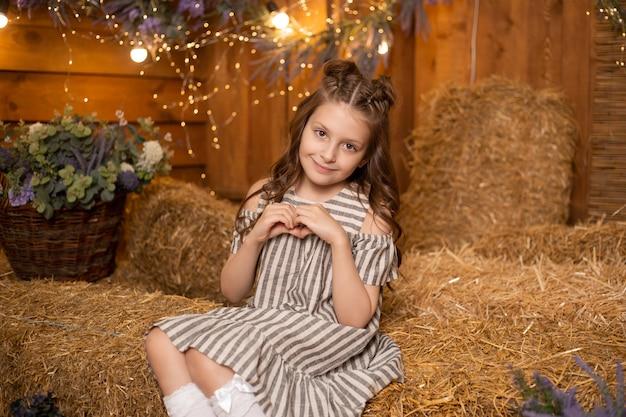 Uma menina sentada em feixes de palha na fazenda usando vestido