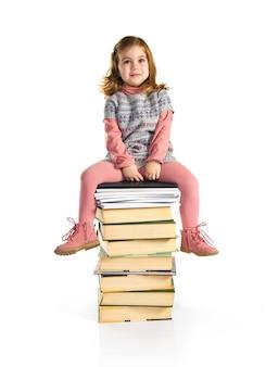 Uma menina sentada em livros. de volta à escola