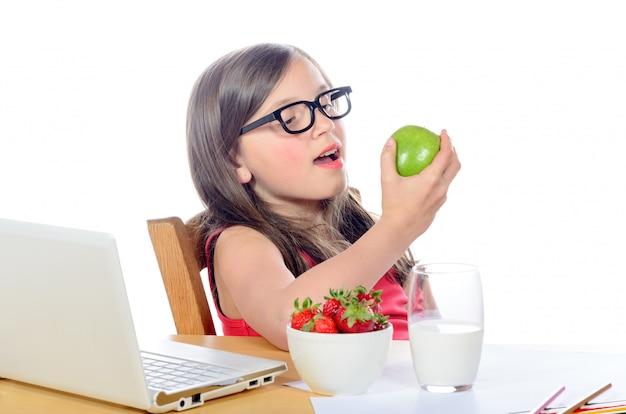 Uma menina sentada em sua mesa, comendo uma maçã