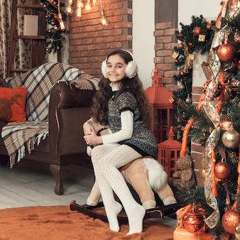 Uma menina sentada em um cavalo de brinquedo na sala de natal decorada