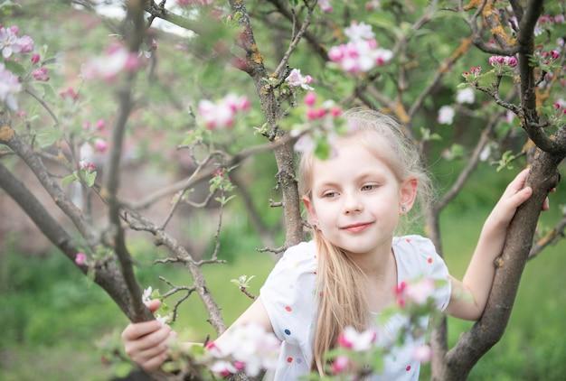 Uma menina sentada em uma árvore em flor no jardim de maçãs