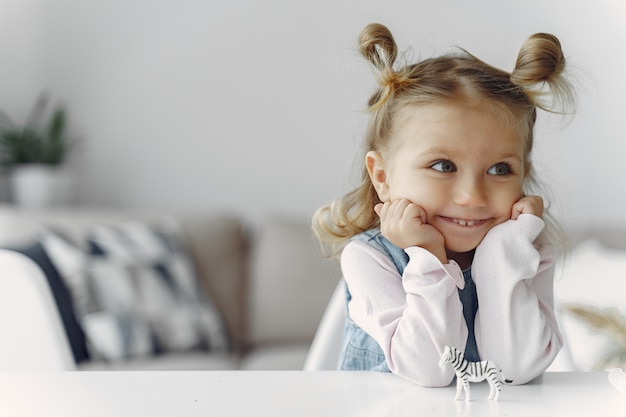 Uma menina sentada em uma mesa com brinquedo