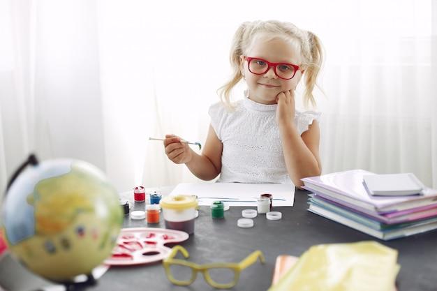 Uma menina sentada em uma mesa e desenho