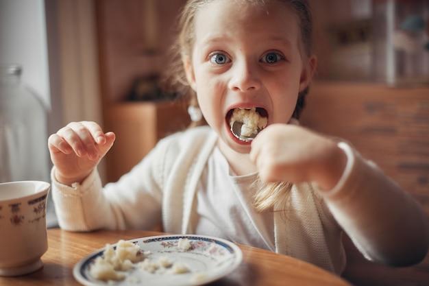 Uma menina sentada em uma mesa na cozinha e comer mingau