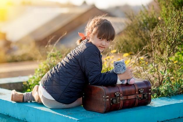 Uma menina sentada em uma plataforma com uma mala vintage ao pôr do sol