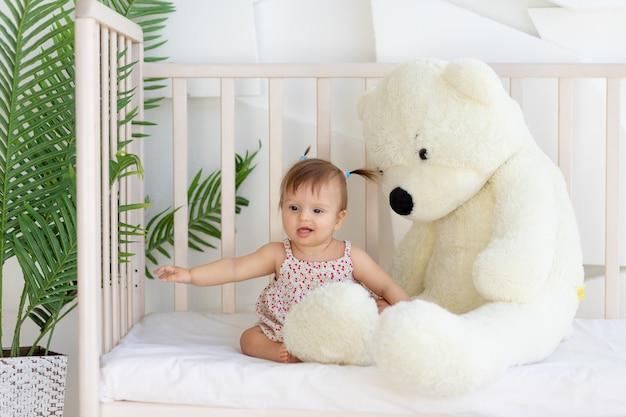 Uma menina sentada em uma sala iluminada em um berço em casa com um grande ursinho de pelúcia